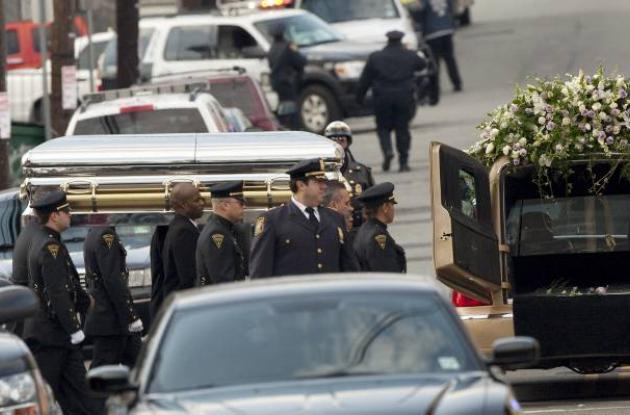Varias personas cargan el ataúd que contiene el cuerpo de Whitney Houston.
