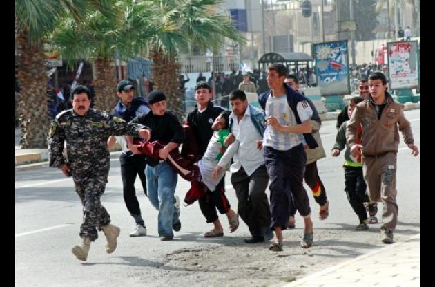 Manifestantes contra el gobierno iraquí llevan a un hombre herido durante los en