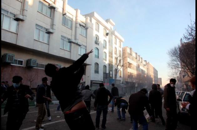 Un manifestante iraní lanza una piedra contra la policía antidisturbios durante