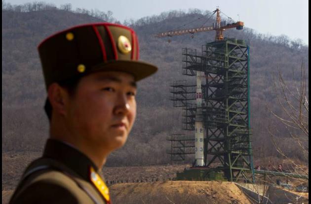 Soldado de Corea del Norte en  frente del Cohete Unha-3 en su lanzamiento