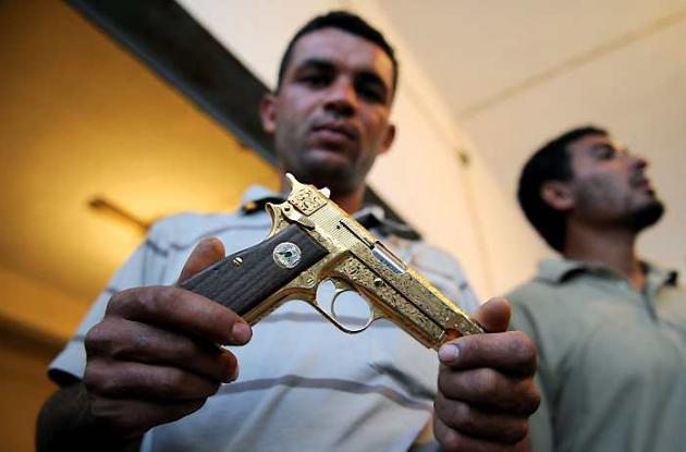La pistola de oro de Gadafi es tomada como un trofeo por los rebeldes.