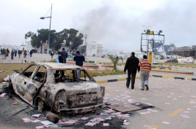 Residentes se ven caminar más allá de un vehículo quemado en Benghazi, Libia.