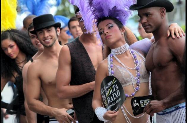 Desfile de modelos en ropa interior frente a una terminal de autobuses con motiv