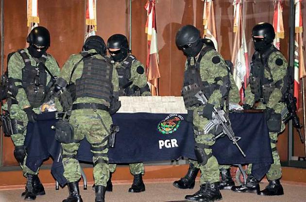 Soldados llevan una tabla que muestra montones de dólares en una presentación de