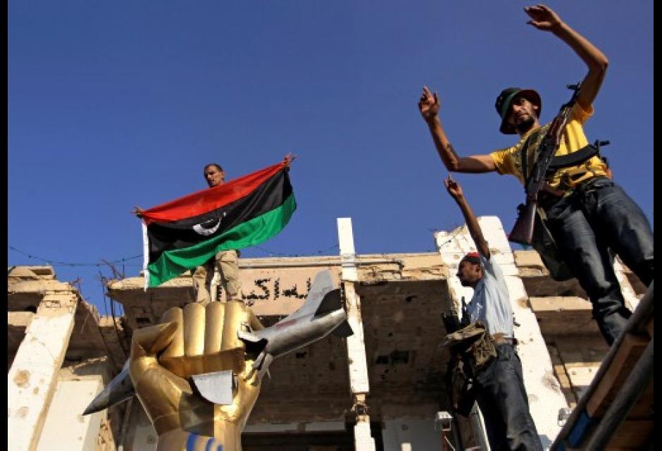 Rebeldes sobre estatua de Gadafi