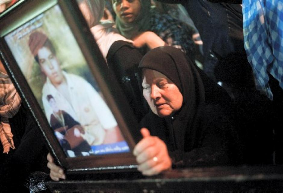 Mujer muestra imagen de su hijo asesinado por el régimen de Gadafi