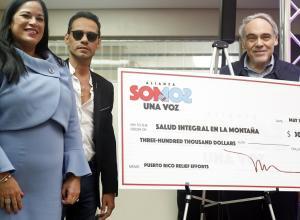 El cantante estadounidense de padres puertorriqueños, Marc Anthony (c), posa acompañado por la directora ejecutiva del ente puertorriqueño Salud Integral en la Montaña (SIM), Gloria Del Carmen Amador (i), y el el presidente emérito y cofundador de The Children's Health Fund (CHF), Irwin Redlener (d), con el cheque de 300 mil dólares que donó junto a la clínica móvil hoy, jueves 10 de mayo de 2018, en Orocovis (Puerto Rico).