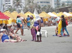 Vendedores ambulantes le ofrecen su servicio a turistas en las playas de Cartagena.